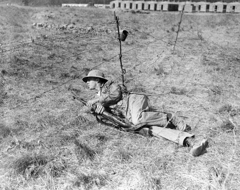 A marine private crawls through a barbed wire entanglement at this Marine Corps rifle range where he is undergoing three intensive weeks of rifle instruction. Camp Matthews, 1943.