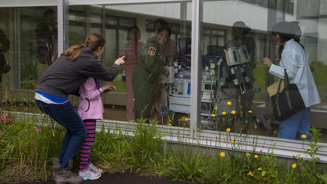 Katherine and Emmeline McKeown, spouse and daughter of U.S. Air Force Capt. Connor McKeown, waves to Oliver McKeown through the Aomori Hospital window prior to the aeromedical evacuation in Aomori, Japan, June 16, 2017. For Emmeline, this was the first time seeing her brother. Once the neonatal intensive care unit team from the U.S. Navy hospital, Okinawa, Japan, prepared Oliver for the flight, they transferred him to the Aomori Airport for departure. (U.S. Air Force photo by Senior Airman Deana Heitzman)