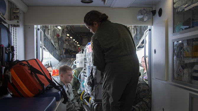 U.S. Air Force Maj. Margaret Dodd, an 18th Medical Operations Squadron neonatal intensive care unit nurse from Kadena Air Base, Japan, assists in lifting Oliver McKeown, son of Capt. Connor McKeown, during an aeromedical evacuation in Aomori, Japan, June 15, 2017. The coordination process had to filter through the Aomori Airport Management Office and Theater Patient Movement Requirements Center, which builds the evacuation mission, sources the aircraft and assigns the aircrew and medical team. (U.S. Air Force photo by Senior Airman Deana Heitzman)