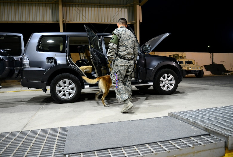 U.S. Air Force Senior Airman Omar Araujo, a military working dog handler and his partner Syrius a military working dog assigned to the 407th Expeditionary Security Forces Squadron search vehicles prior to entering the base in Southwest Asia on May 23, 2017. Araujo and Syrius have been partners for about a year now and are deployed in support of Operation Inherent Resolve. Military working dogs are the first line of defense when it comes to explosive detection and provide security sweeps throughout the installation. (U.S. Air Force photo by Tech Sgt. Andy M. Kin)