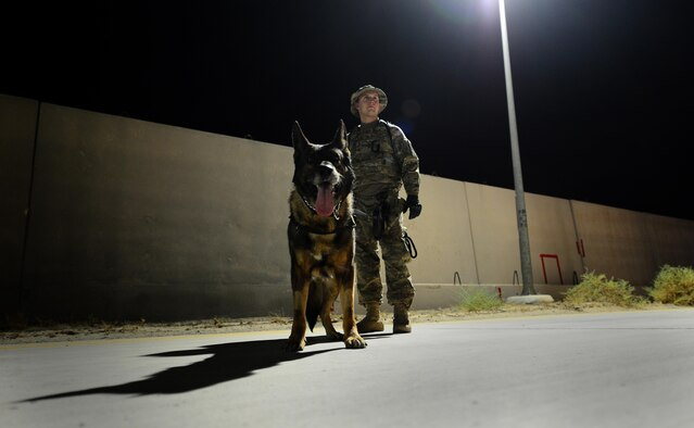 U.S. Air Force Senior Airman Carlton Isaacson, a military working dog handler assigned to the 407th Expeditionary Security Forces Squadron and his partner Egon, patrol the flightline on May 23, 2017, in Southwest Asia. Isaacson and Egon have been partners for two years now and are deployed in support of Operation Inherent Resolve. Military working dogs are the first line of defense when it comes to explosive detection and provide security sweeps throughout the installation. (U.S. Air Force photo by Tech. Sgt. Andy M. Kin)