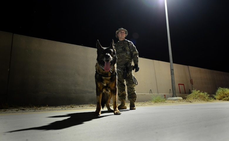 U.S. Air Force Senior Airman Carlton Isaacson, a military working dog handler assigned to the 407th Expeditionary Security Forces Squadron and his partner Egon, patrol the flightline in Southwest Asia on May 23, 2017. Isaacson and Egon have been partners for two years now and are deployed in support of Operation Inherent Resolve. Military working dogs are the first line of defense when it comes to explosive detection and provide security sweeps throughout the installation. (U.S. Air Force photo by Tech Sgt. Andy M. Kin)