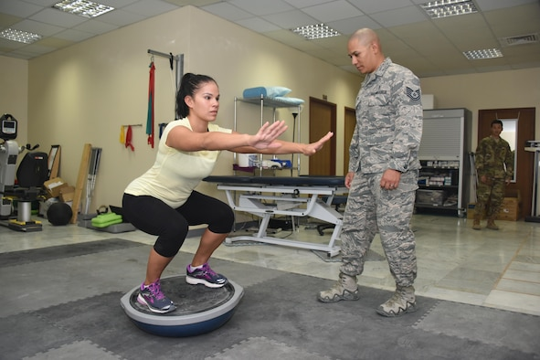 Tech. Sgt. David Garcia (middle), the NCOIC of physical therapy, 386th Expeditionary Medical Group, monitors the form of Staff Sgt. Melanie Hernandez, a patient with the 386th EMDG physical therapy clinic, as she performs squats on a stability ball during a physical therapy session at an undisclosed location in Southwest Asia, June 11, 2017. The physical therapy clinic provides an array of rehabilitative services to promote movement, reduce pain, restore function and prevent disability of injured military personnel. (U.S. Air Force photo/ Tech. Sgt. Jonathan Hehnly)