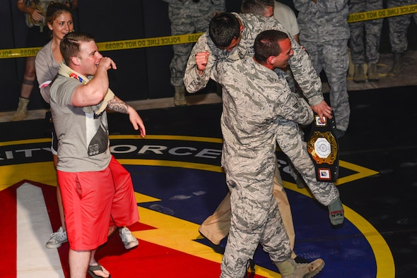 Members from the 35th Security Forces Squadron congratulate Airman Sergio Miranda, a 35th SFS entry controller, after winning the belt and title of the 2017 Combatives Champion during the second annual Security Forces Advanced Combat Skills Assessment held at the Security Forces Regional Training Center at Andersen Air Force Base, Guam, June 8, 2017. More than 100 Airmen and Soldiers throughout U.S. Pacific Command's area of responsibility gathered to compete in five different categories: weapons, tactics, combat fitness, mental and physical challenge and military working dog handling. (U.S. Air Force photo/Airman 1st Class Christopher Quail)