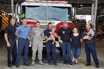 The Shupperd family visited Grissom fire station to thank the team for saving their son's life, May 23. Listed from left to right: Jay Salmons, Tom Carey, Airman 1st Class Andrew Smith, Robert Jacobs holding Waylon Shupperd, Brandon Shupperd, Megan Shupperd and David Perryman holding their youngest son Maverick Shupperd. (Courtesy photo)
