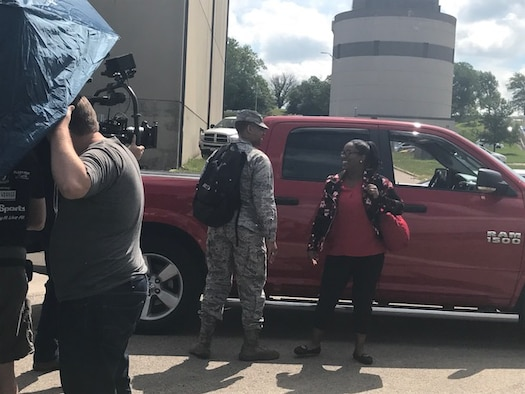 """Jasmine Moore, 88th Force Support Squadron education and training Pathway intern, and husband Lt. Calvin Moore, Air Force Life Cycle Management Center program manager, film a scene arriving to work together for the PACE's """"Teamwork"""" Heritage Today video on June 8, 2017. The video will feature Air Force civilians and their contributions to the Air Force mission. (U.S. Air Force photo/Stacey Geiger)"""