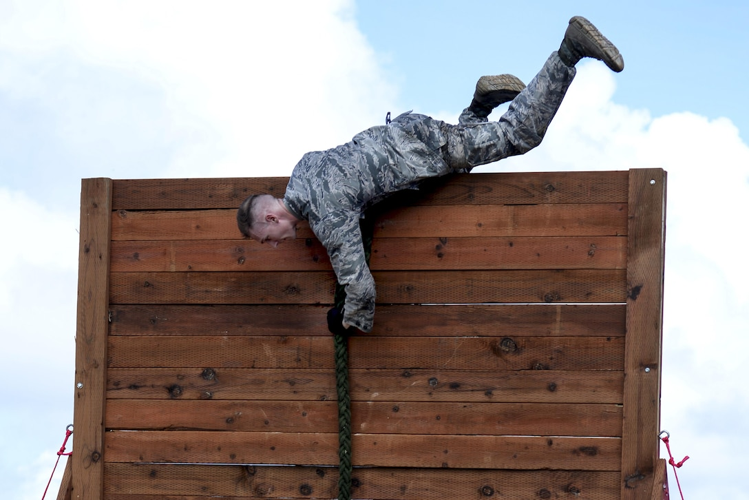 Capt. Kyle Buss, the 36th Security Forces Squadron operations officer, climbs over a wall during the second annual Security Forces Advanced Combat Skills Assessment June 6, 2017, at Andersen Air Force Base, Guam. The mental and physical challenge portion tested basic combat skills and knowledge of competitors at different stations along an obstacle course through the jungle. (U.S. Air Force photo/Airman 1st Class Gerald R. Willis)