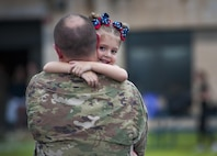 Staff Sgt. Matthew Pearson, a 71st Aircraft Maintenance Unit navigation specialist, holds his daughter, Savannah, during a redeployment, June 6, 2017, at Moody Air Force Base, Ga. The 41st and 71st Rescue Squadrons were recently deployed to Southwest Asia where they provided combat search and rescue capabilities in support of Operation Inherent Resolve. (U.S. Air Force photo/Airman 1st Class Lauren M. Sprunk)