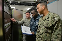 Tech. Sgt. Jonathan Brown, Petty Officers 1st Class Clinton Jordan and Brian Blodgett, 364th Training Squadron Digital Voice Switching course students perform an overview of hardware documentation on the DMS-100 at Sheppard Air Force Base, Texas. This course provides an introduction to major areas of digital switches for identification of telephone exchange switch equipment. (U.S. Air Force photo by Liz H. Colunga/Released)
