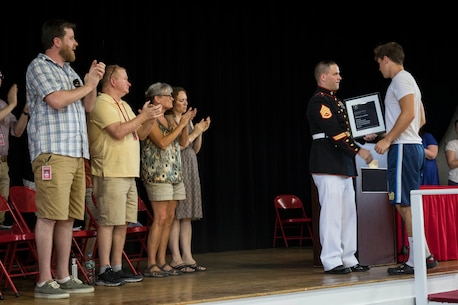 Staff Sgt. James Ralstin presents Michael Lunny, a junior with Sanford High School in Sanford, Maine, with a plaque commemorating his Semper Fidelis All-American Program selection during an award ceremony at the school, June 13, 2017. Lunny will be one of less than 100 nominees attending the Battles Won Academy, a Marine Corps leadership and networking seminar in Washington, D.C. Ralstin is a canvassing recruiter for Recruiting Substation Dover, N.H.