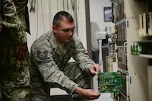 Tech. Sgt. Jonathan Brown, 364th Training Squadron Digital Voice Switching course student inspects a circuit panel on the DMS-100 at Sheppard Air Force Base, Texas. This course provides an introduction to major areas of digital switches for identification of telephone exchange switch equipment. (U.S. Air Force photo by Liz H. Colunga/Released)
