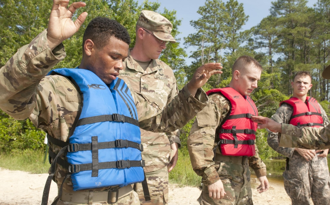 Pfc. Andrew Green (left), an Army paralegal representing the Army Reserve Legal Command, is among a group of  Warriors preparing to swim with rifles across a 300-meter lake as part of the 2017 U.S. Army Reserve Best Warrior Competition at Fort Bragg, N.C. June 15. This year's Best Warrior Competition will determine the top noncommissioned officer and junior enlisted Soldier who will represent the U.S. Army Reserve in the Department of the Army Best Warrior Competition later this year at Fort A.P. Hill, Va. (U.S. Army Reserve photo by SGT David Turner) (Released)