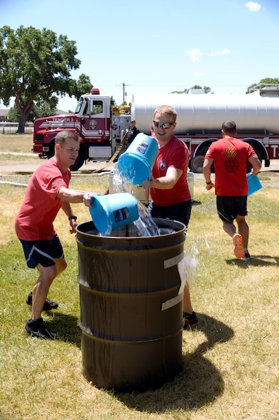 Col. Scott Bell and Capt. Thurmond Jackson, both from Munitions Sustainment Division Team 1, take part in a bucket brigade competition where teams of four fill up 55-gallon drums with water in the shortest possible amount of time. Teams of Airmen from across the base took part in an annual fire muster, which was held at Centennial Park on Hill Air Force Base, June 14, 2017. (Todd Cromar/U.S. Air Force)