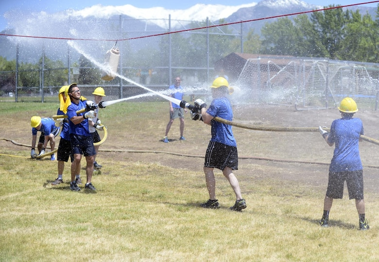 Team 'F-16 SPO' faced off against team 'Diamonds and Pearl' during a 'make or break' competition where each team must roll out fire hoses, connect a nozzle and use the hose to push a hanging bucket to their opponents side, and then break down and roll up their hose. Teams of Airmen from across the base took part in an annual fire muster, which was held at Centennial Park on Hill Air Force Base, June 14, 2017. (Todd Cromar/U.S. Air Force)