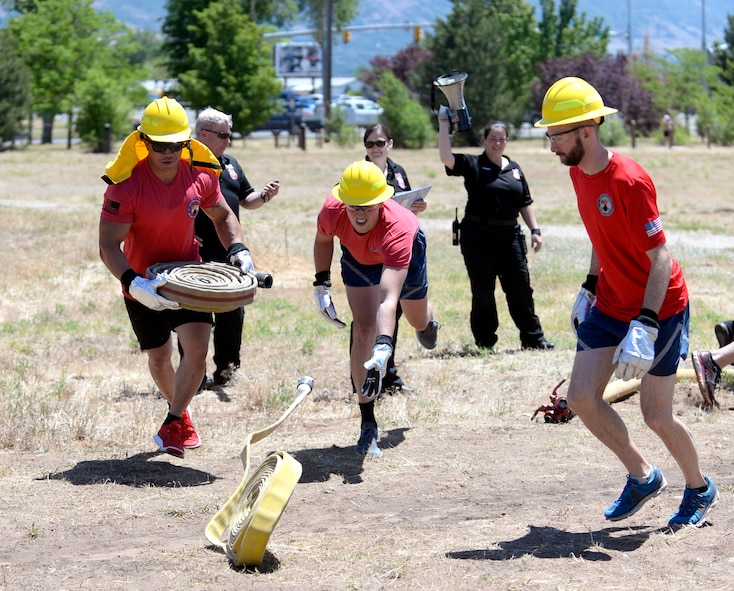 From the left, Staff Sgt. Justin Southichack, 2nd Lt. Caleb Mild and Devin Swanson, all from the 'Munitions Sustainment Division Team 2' begin the 'make or break' competition where each team must roll out fire hoses, connect a nozzle and use the hose to push a hanging bucket to their opponents side, and then break down and roll up their hose. Teams of Airmen from across the base took part in an annual fire muster, which was held at Centennial Park on Hill Air Force Base, June 14, 2017. (Todd Cromar/U.S. Air Force)
