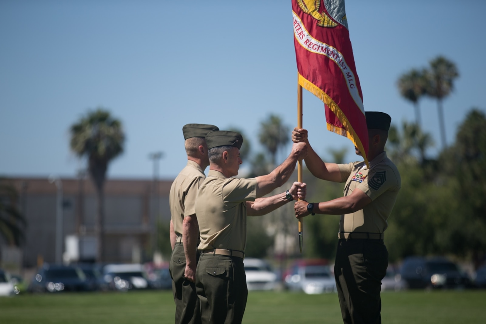 U.S. Marine Col. Phillip N. Frietze (center) exchanges the regimental colors with Col. James R. Hensein (left) during the Headquarters Regiment, 1st Marine Logistics Group, change of command ceremony on Camp Pendleton, Calif., June 15, 2017. The ceremony included marching of the colors, passing of the regimental colors, presenting Col. Frietze his away and closing remarks from the oncoming and off going personnel as well as the 1st Marine Logistics Group Commanding General, Brig. Gen. David A. Ottignon. (U.S. Marine Corps photo by Lance Cpl. Timothy Shoemaker)