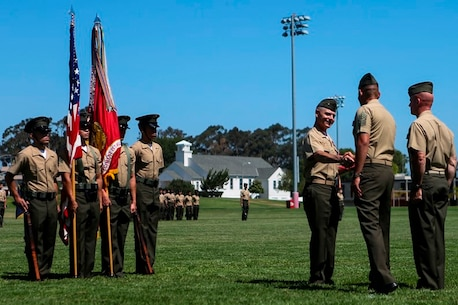 U.S. Marine Col. Phillip N. Frietze (left) and Sgt. Major Carlos A. Ruiz (right) shake hands after Frietze receives his award at the 1st Marine Logistics Group Headquarters Regiment Change of Command on Camp Pendleton, Calif., June 15, 2017. The ceremony included marching of the colors, passing of the regimental colors, presenting Frietze his award and closing remarks from the oncoming and off going personnel as well as the 1st MLG Commanding General, Brig. Gen. David A. Ottignon. (U.S. Marine Corps photo by Lance Cpl. Joseph Sorci)