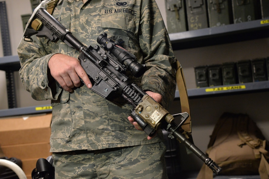 Senior Airman Tyler Merrill, 341st Security Forces Support Squadron armorer, demonstrates the proper holding of a weapon June 9, 2017, at Malmstrom Air Force Base, Mont. Fingers should be kept outside the trigger guard or along the side of the weapon until ready to shoot. (U.S. Air Force photo/Airman 1st Class Daniel Brosam)
