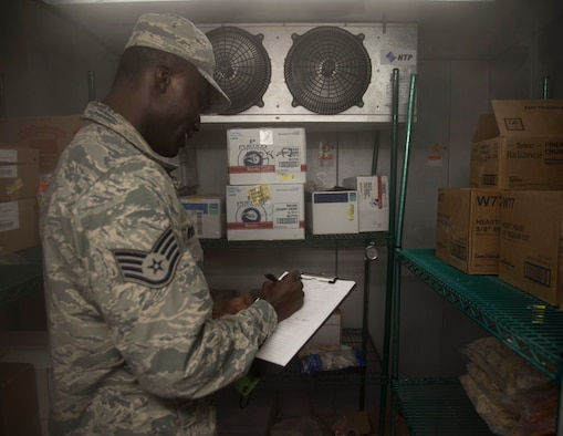 U.S. Air Force Staff Sgt. Cornelius Bransah, the NCO in charge of food safety and sanitation assigned to the 6th Aerospace Medical Squadron, writes down notes after inspecting a walk-in freezer at MacDill Air Force Base, Fla., June 13, 2017. Bransah checks dates, as well as the temperature of the freezer to ensure proper food safety. (U.S. Air Force photo by Airman 1st Class Adam R. Shanks)