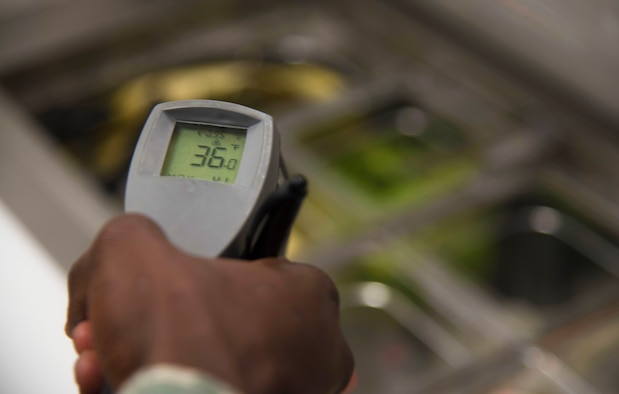 U.S. Air Force Staff Sgt. Cornelius Bransah, the NCO in charge of food safety and sanitation assigned to the 6th Aerospace Medical Squadron, uses a handheld infrared thermometer to check the temperatures of food items at MacDill Air Force Base, Fla., June 13, 2017. Bransah inspects in accordance to the Tri-Service Food Code to make sure food prepared on MacDill is at the correct temperature. (U.S. Air Force photo by Airman 1st Class Adam R. Shanks)