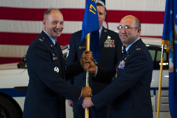 U.S. Air Force Col. Christopher Harris, 17th Mission Support Group Commander, passes the unit guideon to Col. Michael Downs, 17th Training Wing Commander, during the 17th MSG Change of Command ceremony at the Logistics and Readiness High Bay on Goodfellow Air Force Base, Texas, June 16, 2017. The event honored Harris's service to his unit and welcomed its new commander, Col. Jason Beck. (U.S. Air Force photo by Senior Airman Scott Jackson/Released)