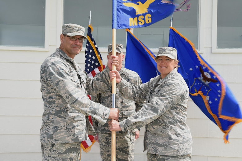 Colonel Stephen Kravitsky, 90th Missile Wing commander, passes the guidon to Col. Tricia Van Den Top, 90th Mission Support Group commander, during the 90th MSG Change of Command ceremony June 16, 2017, on the Argonne Parade Field at F.E. Warren Air Force Base, Wyo. The ceremony signified the transition of command from Col. Frank Verdugo to Van Den Top. (U.S. Air Force photo by Glenn S. Robertson)