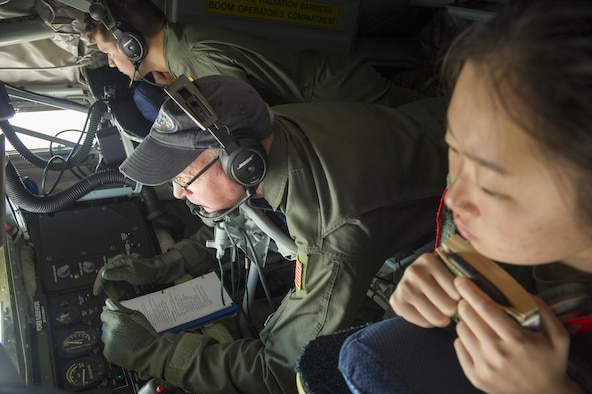 Two cadets from the U.S. Air Force Academy observe Senior Master Sgt. Jim Martin, 314th Air Refueling Squadron boom operator, as he prepares for a refueling trainer mission June 9, 2017. Cadets were given an incentive flight to learn more about the operational Air Force as part of their Ops Air Force tour. (U.S. Air Force photo by Senior Airman Tara R. Abrahams)