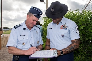 Air Force Chief of Staff Gen. David Goldfein, signs oath of enlistment paperwork for Senior Master Sgt. Steven Beasley, 737th Training Group superintendent of standardization and evaluation, prior to the start of basic military training graduation June 16, 2017, at Joint Base San Antonio-Lackland. Goldfein toured various JBSA-Lackland facilities and met many 37th Training Wing Airmen during his two-day visit. Beasley joined BMT Airmen in reciting the oath as Goldfein administered during the graduation. (U.S. Air Force photo by Johnny Saldivar)