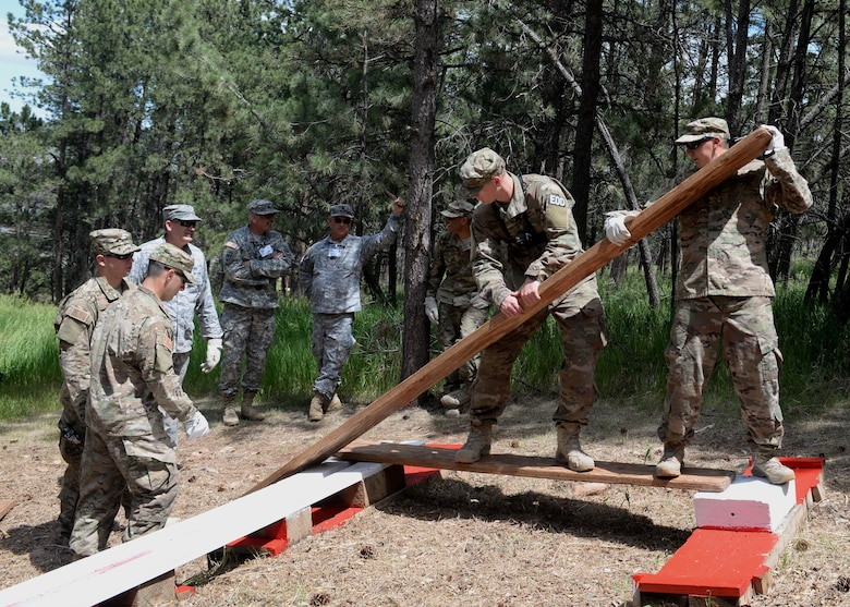 Airmen from the 28th Civil Engineer Squadron work together to complete an obstacle course during the Leadership Reaction Course at Camp Rapid, Rapid City, South Dakota, June 14, 2017. The LRC is designed to build teamwork and leadership skills by completing various obstacles. (U.S. Air Force photo by Airman 1st Class Thomas I. Karol)