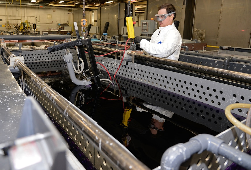 Sebastian Harrelson, an electroplater in the 309th Commodities Maintenance Group, prepares to submerge the nose gear of an F-16 at Hill Air Force Base, Utah. The organization is overhauling an increasing number of landing gear components with a more eco-friendly coating because of a new process developed by Utah-based ES3 under the Air Force SBIR/STTR Program. The coating - made possible by the new application process - has been shown to provide better protection for components and is expected to yield significant savings over the environmental cleanup needed for traditional coatings. (U.S. Air Force Photo/Alex R. Lloyd)