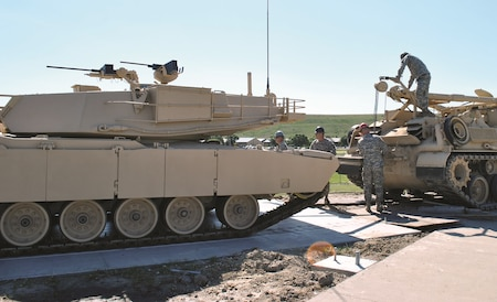 """Soldiers of the 1st Infantry Division Sustainment Brigade place a M1 Abrams Main Battle Tank onto its concrete pad just behind the Henry Gate at building 800 May 25. The M1 was transported from Douthit Gunnery Complex in February to a workshop to be cleaned up and painted by Soldiers prior to being placed on the pad. In the coming weeks, it will be detailed to include the 1st Infantry Division insignia in celebration of the 100th birthday of the """"Big Red One."""" The transportation, restoration and creation of the M1 and display area were made possible through the joint efforts of Soldiers and personnel of organizations such as the Directorate of Plans, Training, Security and Mobilization; Directorate of Public Works; Department of Emergency Services; Logistics Readiness Center; Maneuver Area Training Equipment Site and others."""