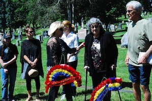 Laura Hegeman, niece of WWII casualty Pfc. Silvio Campanella, assists Campanella's surviving sister, Yolanda Campanella Robilotto and other family members to view the memorial wreaths and newly placed headstone at the rededication ceremony of Campanella's graveside at the St. Agnes Cemetery in Albany, N.Y. June 14, 2017. The Rainbow Division Veterans Foundation helped coordinate the memorial ceremony and Soldiers of the 42nd Infantry Division Headquarters provided colors and honors. U.S. National Guard photo by Col. Richard Goldenberg.