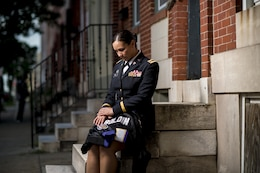 Chief Warrant Officer 2 Jennifer Pace holds her brother's Baltimore Ravens jersey for a portrait in West Baltimore, Maryland, June 15, where she used to work as a police officer before committing her career full time to the U.S. Army Reserve. Pace is among this year's recipients of the General Douglas MacArthur Leadership Award, which she won as a property book officer while working for the 290th Military Police Brigade, headquartered in Nashville, Tennessee. In her leadership journey and professional growth, Pace overcame the loss of her brother, Danny Gamez, who passed away in 2011. (U.S. Army Reserve photo by Master Sgt. Michel Sauret)