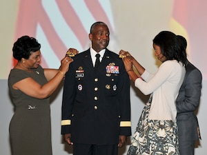 DLA Director Army Lt. Gen. Darrell Williams receives his three-star shoulder boards from (left-right) his wife Myra and his children.