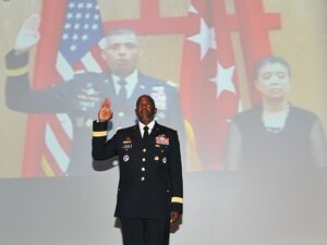 DLA Director Army Lt. Gen. Darrell Williams takes the oath of office, administered by Army Gen. Vincent Brooks (on screen), commander of U.S. Forces Korea, with wife Carol Brooks at right.