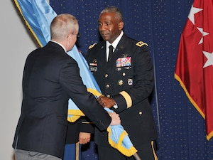 James MacStravic, performing the duties of the under secretary of defense for acquisition, technology and logistics, passes the Defense Logistics Agency command flag to the agency's new director, Army Lt. Gen. Darrell Williams.