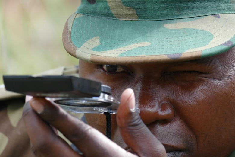 A Zambian Air Force Airman uses a compass during survival training in Lusaka, Zambia, May 30, 2017. Partner nation engagement in air mobility operations helps increase the capacity in humanitarian assistance, regional stability and peacekeeping operations. (U.S. Air Force photo by Tech. Sgt. Gustavo Gonzalez/RELEASED)