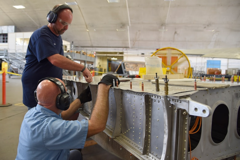 "DAYTON, Ohio (06/2017) -- (From left to right) Restoration Specialists Duane Jones and Roger Brigner work on the B-17F ""Memphis Belle""™ in the restoration hangar at the National Museum of the U.S. Air Force. The exhibit opening for this aircraft is planned for May 17, 2018.(U.S. Air Force photo by Ken LaRock)"