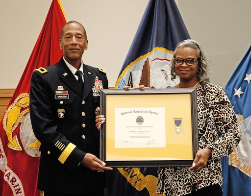 DLA Troop Support Commander Army Brig. Gen. Charles Hamilton recognizes Deborah Cromwell-Bush as the DLA Director's Strategic Process Excellence Goal winner for the first quarter of fiscal 2017 during a ceremony in DLA Troop Support's auditorium June 6. The award cited her numerous accomplishments, including her design of four centralized, user friendly databases used to track, categorize and manage contracting workloads within the Industrial Hardware supply chain.