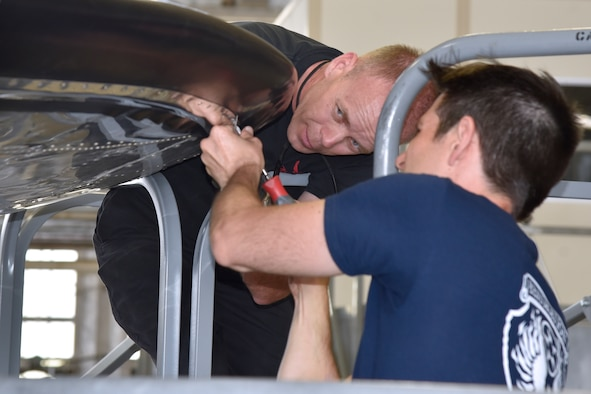 """DAYTON, Ohio (06/2017) -- (From left to right) Restoration Specialists Brian Lindamood and Casey Simmons work on the B-17F """"Memphis Belle""""™ in the restoration hangar at the National Museum of the U.S. Air Force. The exhibit opening for this aircraft is planned for May 17, 2018.(U.S. Air Force photo by Ken LaRock)"""