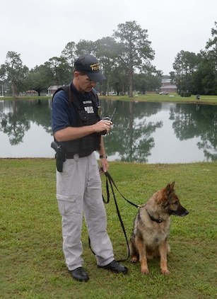"""Cpl. James Medders, police officer/dog handler, Marine Corps Police Department, Marine Corps Logistics Base Albany, and his K-9 Military Working Dog search the perimeter of Covella Pond during a """"Lost-Child"""" full-scale exercise on the installation, June 13. The training scenario included reports that a young boy was seen entering the water at the pond. There were roughly 50-60 personnel from the base as well as the city's mutual partners, who participated in the day-long event."""