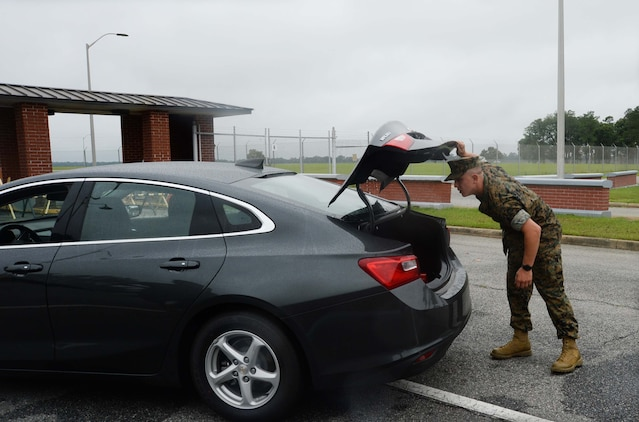 """Cpl. Keaton Kane, Administration Clerk, Military Personnel, Marine Corps Logistics Base Albany, conducts a vehicle search during a """"Lost-Child"""" full-scale exercise on the installation, June 13. The scenario was implemented in collaboration with the city's mutual partners to train participants on reaction and response time in the event an actual occurrence of this type happened. There were roughly 50-60 personnel from the base as well as the city's mutual partners, who participated in the day-long event."""
