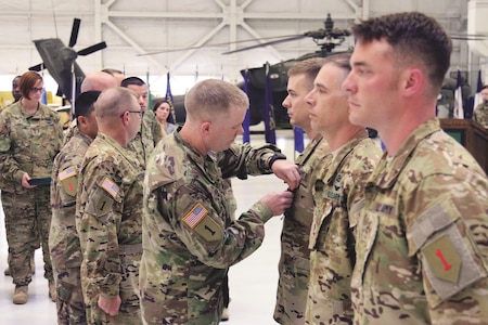 Brig. Gen. Patrick D. Frank, 1st Infantry Division and Fort Riley acting senior commander, awards the Air Medal with Valor to Capt. Eric V. Cornelius, Chief Warrant Officer 3 William Myrick and Chief Warrant Officer 2 Robert S. Adams, pilots with Company A, 1st Attack Reconnaissance Battalion, 1st Combat Aviation Brigade, 1st Inf. Div., May 17 on Marshall Army Airfield for their acts of heroism in Afghanistan. The three pilots put themselves between Taliban fighters and the friendly Afghan ground forces to draw fire so the Afghans could ex-filtrate.