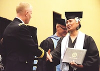 Staff Sgt. Sinalemoana T. Osa, right, is congratulated by Brig. Gen. Patrick D. Frank, Fort Riley and 1st Infantry Division acting senior commander, during the Fort Riley Education Services Commencement Exercise May 25 at the Hilton Garden Inn in Manhattan. Osa graduated with a Bachelor of Science in psychology.