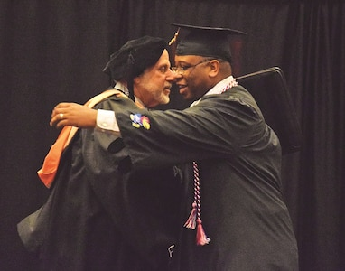 Master Sgt. Darryl B. Williams, right, celebrates with Wallace Meyer Jr., director, Entrepreneurship Program, University of Kansas, after Williams received his degree during the Fort Riley Education Services Commencement Exercise May 25 at the Hilton Garden Inn in Manhattan. Williams graduated with a Certificate in Entrepreneurship.