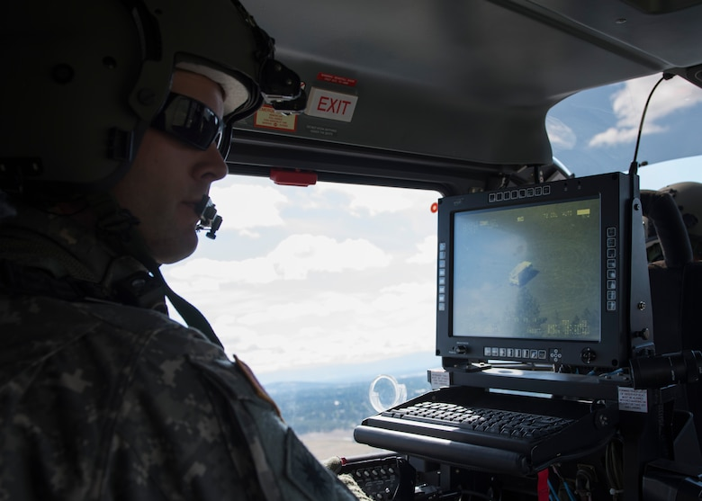 Sgt. Darrell Russell, C Company, 1st Battalion, 112th Airborne Regiment Lakota crew chief, spots a disabled truck using the on-board camera system June 14, 2017, north of Fairchild Air Force Base, Washington. The Lakota is equipped with a nose mounted camera system that gives the light aircraft the ability to spot and lock onto targets from long distances.