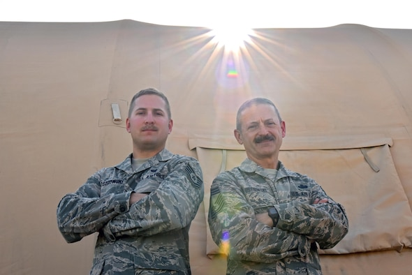 Tech. Sgt. Tyler Ostrowski, left, and Chief Master Sgt. Ted Ostrowski, Sr., stand outside of a tent at an undisclosed location in Southwest Asia, June 16, 2017. Ted and Tyler will spend Father's Day deployed with the 380th Air Expeditionary Wing in support of Combined Joint Task Force - Operation Inherent Resolve. (U.S. Air Force photo by Staff Sgt. Marjorie A. Bowlden)