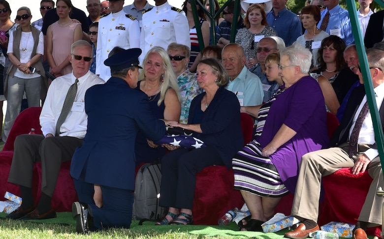 Lynn Evans, niece of John Dean Armstrong, a Flying Tiger, is presented a flag during Armstrong's funeral, June 17, 2017, in Hutchinson, Kan. Evans was presented with a current American flag and a flag from Armstrong's time in the American Volunteer Group. (U.S. Air Force photo/Staff Sgt. Trevor Rhynes)