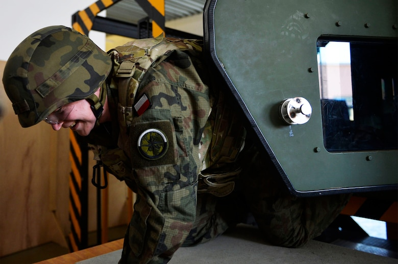 Capt. Ewa Betke, training branch officer for the Hydrometeorological Service of the Polish Armed Forces, exits a Humvee egress assistance trainer on Lucius D. Clay Kaserne, Germany, June 14, 2017. German, Hungarian, and Polish, troops participated with U.S. Airmen in Exercise Cadre Focus 17-1. The 7th Weather Squadron conducts the exercise to enhance its Airmen's ability to cooperative with the U.S. Army (U.S. Air Force photo by Airman 1st Class Joshua Magbanua).