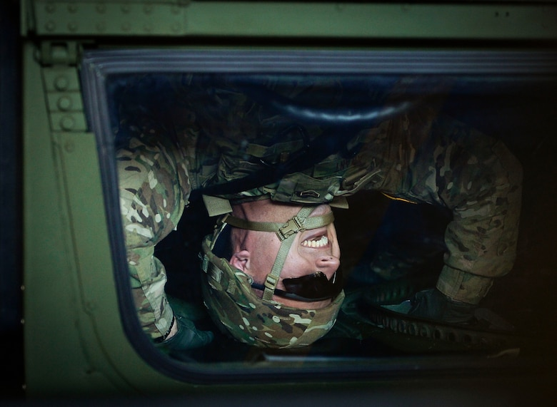 U.S. Air Force Airman 1st Class Athon Arant, 7th Weather Squadron weather apprentice, laughs as he flips upside-down in a Humvee egress assistance trainer on Lucius D. Clay Kaserne, Germany, June 14, 2017. HEAT simulators are designed to imitate a Humvee rolling over. The 7th WS regularly trains its Airmen to enhance their capabilities of working with the U.S. Army. (U.S. Air Force photo by Airman 1st Class Joshua Magbanua)